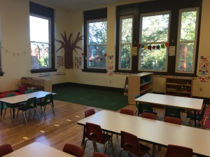 A classroom with four small tables and lots of windows